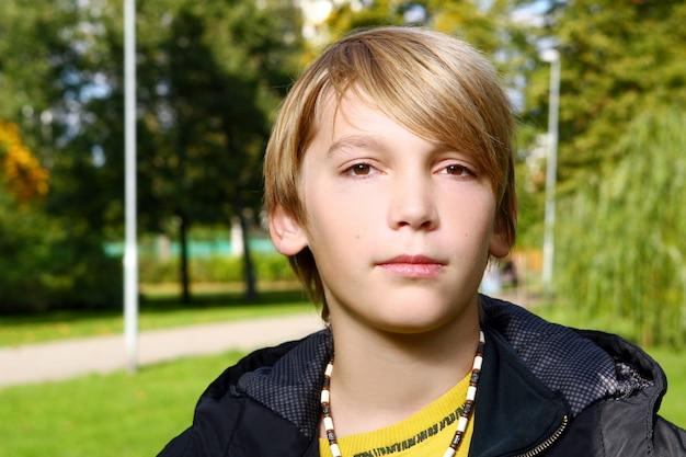 Menino loiro atraente posando no parque Foto gratuita