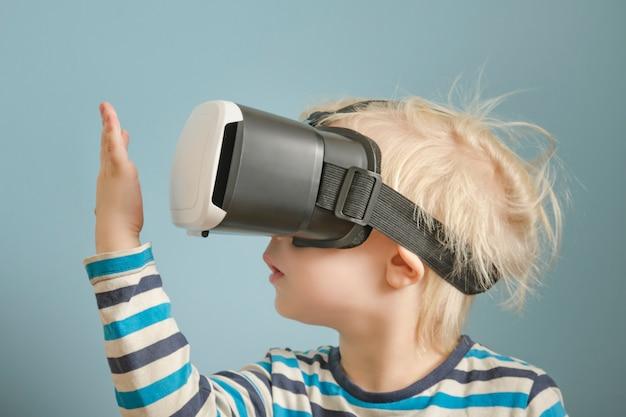 Menino loiro com óculos de realidade virtual Foto Premium