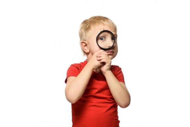 Menino loiro com uma lupa nas mãos Foto Premium