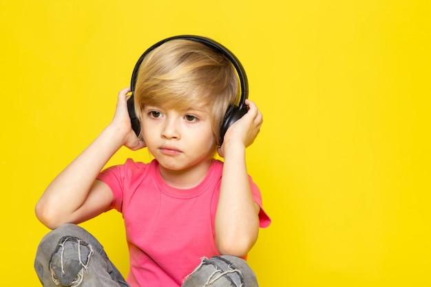 Menino loiro de camiseta rosa e calça jeans cinza em fones de ouvido pretos, ouvindo música Foto gratuita