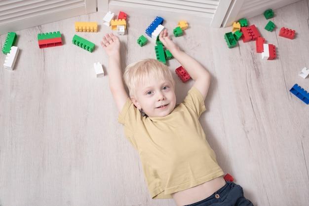 Menino loiro encontra-se no chão entre os blocos de construção Foto Premium