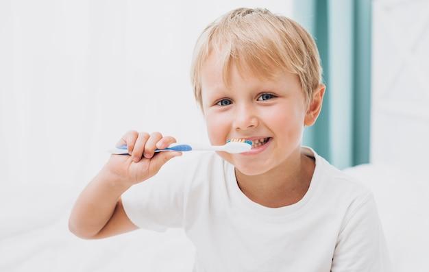 Menino loiro escovando os dentes Foto gratuita