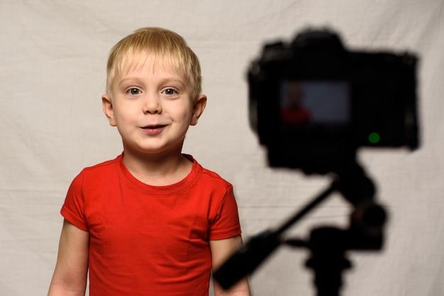 Menino loiro sorridente na frente da lente da câmera. pequeno blogueiro de vídeo. estúdio em casa Foto Premium