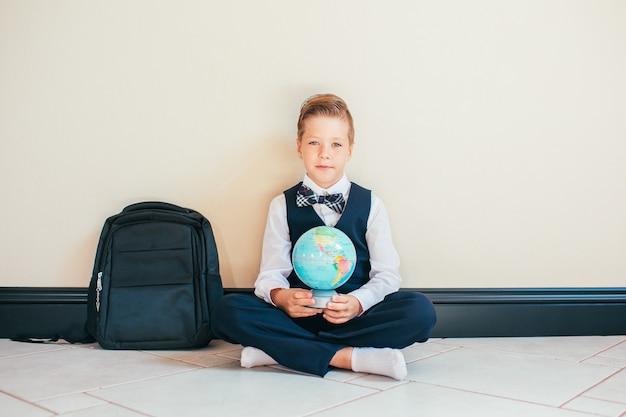 Menino loiro vestido com uniforme escolar, sentada no chão com um globo e olha para a câmera. conceito de educação e viagens. Foto Premium