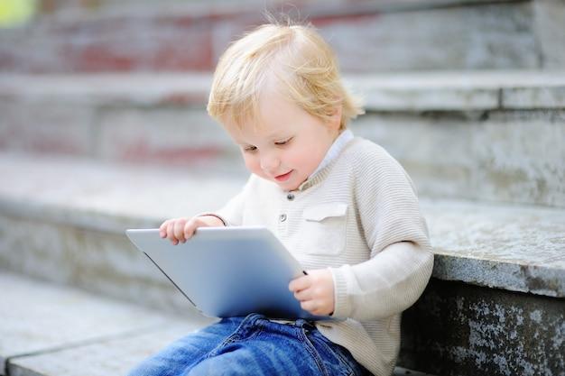 Menino louro bonito da criança que joga com uma tabuleta digital ao ar livre. gadget para criancinhas Foto Premium