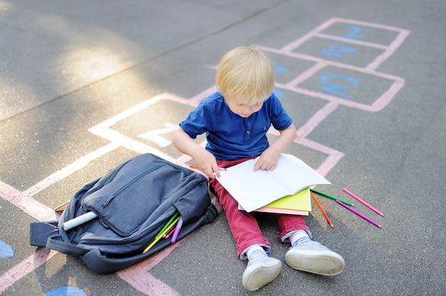 Menino louro bonito que faz os trabalhos de casa que sentam-se na jarda de escola após a escola com os sacos que colocam próximo. Foto Premium