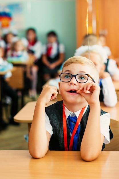 Menino louro com os vidros pretos grandes que sentam-se na sala de aula, studing, sorrindo. educação na escola primária, primeiro dia na escola Foto Premium