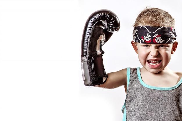 Menino lutando em luvas de boxe e bandana na luz Foto Premium