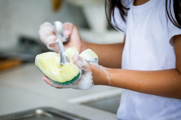 Menino mão lavando colher sobre a pia na cozinha Foto Premium