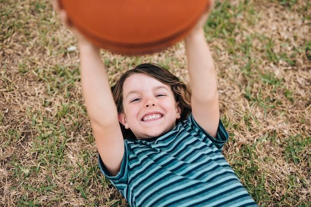 Menino, mentir grama, e, segurando bola Foto gratuita