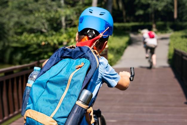 Menino, montando uma bicicleta, parque Foto gratuita