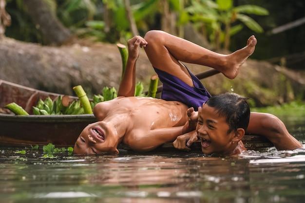 Menino nadando no cannal perto do mercado flutuante de damnoen saduak Foto Premium