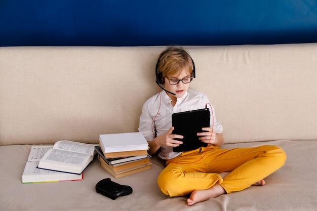 Menino no auto-isolamento usando tablet digital para trabalhos de casa, para pesquisar informações na internet, distância social, aprendendo a educação on-line. conceito de cuidados de saúde. Foto Premium