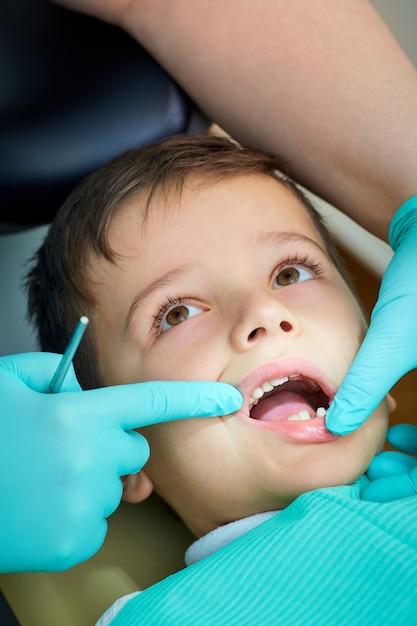Menino no dentista a recepção abriu a boca em clini Foto Premium