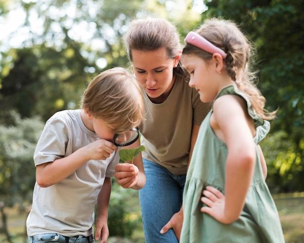 Menino olhando para folhas com lupa Foto gratuita