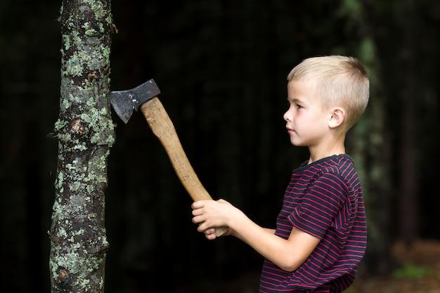 Menino pequeno com o trunfo de árvore velho pesado do corte do machado do ferro na floresta no dia de verão. atividades ao ar livre e trabalho físico. Foto Premium