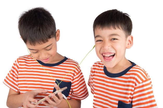 Menino pequeno irmão jogando jogo no celular juntos Foto Premium