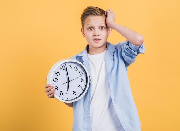 Menino preocupado com a mão na cabeça, segurando o relógio branco de pé contra um fundo amarelo Foto gratuita