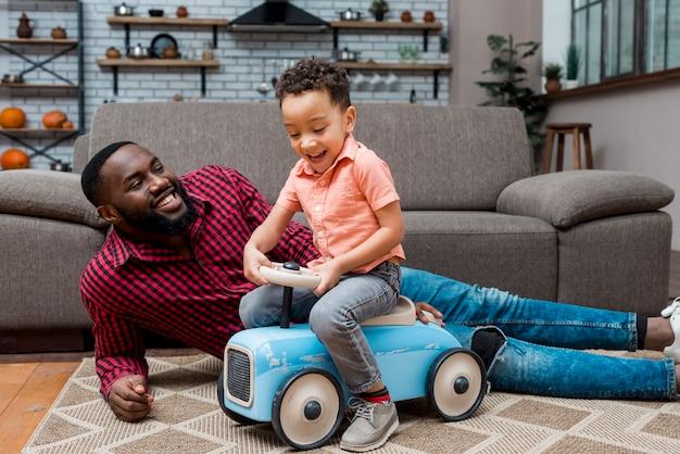 Menino preto, dirigindo, carro brinquedo, com, pai Foto gratuita