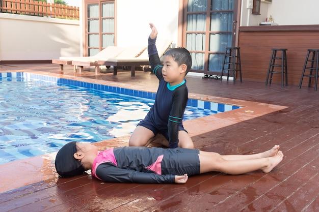 Menino que ajuda afogando a menina da criança na piscina fazendo o cpr. Foto Premium