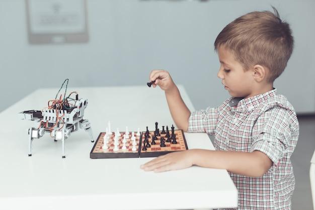 Menino que joga a xadrez com um robô pequeno na tabela. Foto Premium