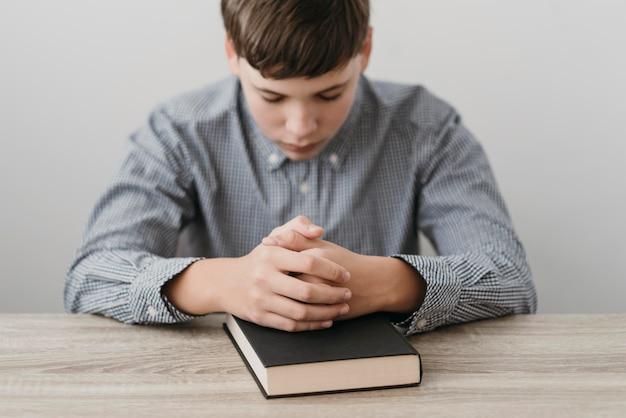 Menino rezando com as mãos na bíblia Foto gratuita