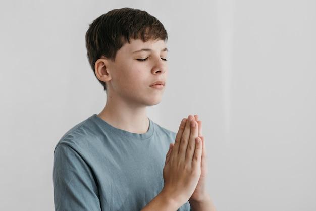 Menino rezando dentro de casa Foto gratuita