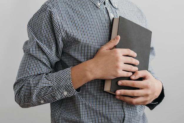 Menino rezando enquanto segura um livro sagrado Foto Premium