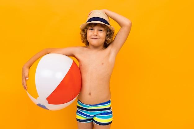 Menino ruivo com um chapéu de verão e um círculo de natação em um fundo amarelo Foto Premium