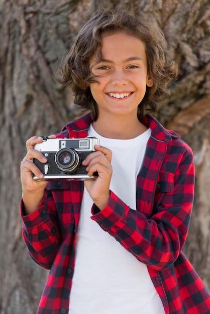Menino segurando a câmera enquanto está ao ar livre com os pais Foto gratuita