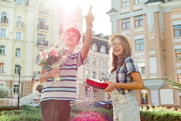 Menino, segurando, buquê flores, e, menina, com, presente, em, caixa Foto Premium