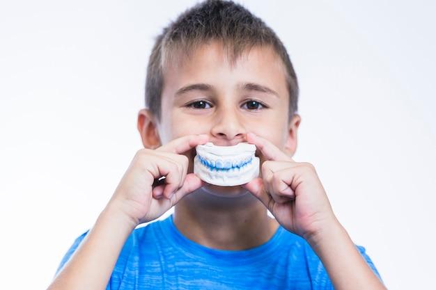 Menino segurando o molde de gesso de dentes no fundo branco Foto gratuita