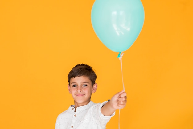 Menino, segurando, um, azul, balloon Foto gratuita