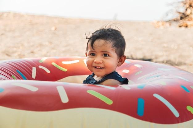 Menino, sentando praia, em, inflável, círculo Foto gratuita