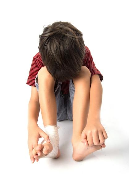 Menino sofre um acidente com a perna e precisa de curativo para primeiros socorros Foto Premium
