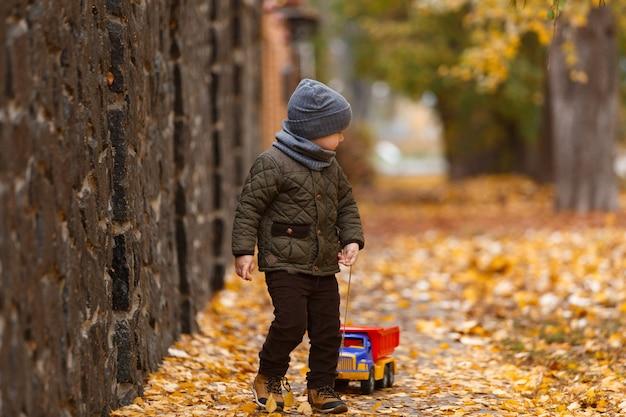 Menino sorridente andando e brincando com o carro de brinquedo ao ar livre no outono. conceito de infância feliz. retrato de criança engraçada Foto Premium