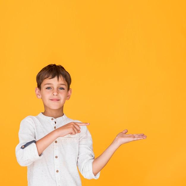 Menino sorridente apontando em uma direção com espaço de cópia Foto gratuita