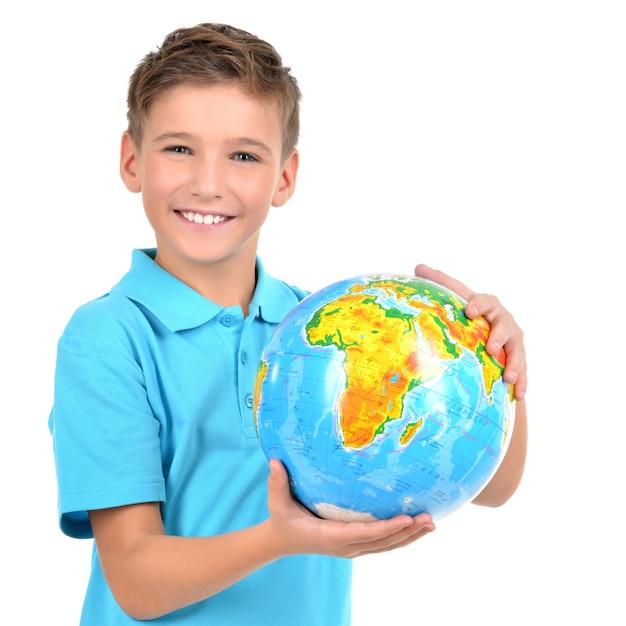 Menino sorridente casual segurando o globo nas mãos - isolado no branco Foto gratuita
