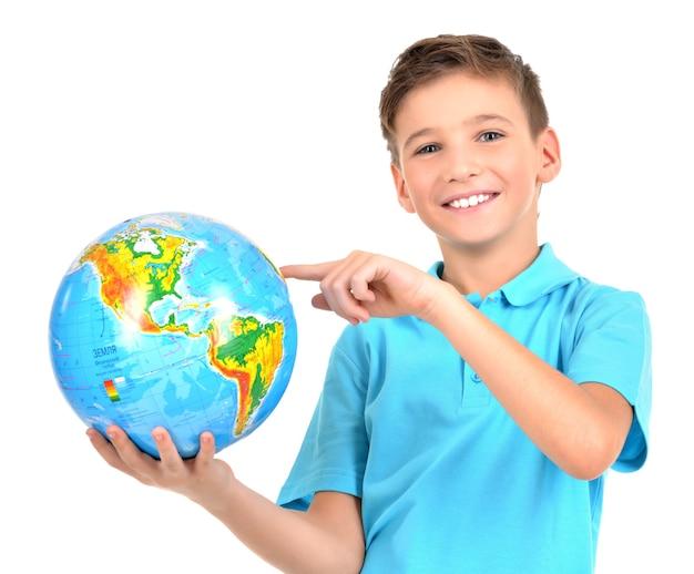Menino sorridente casual segurando um globo nas mãos, isolado no branco Foto gratuita