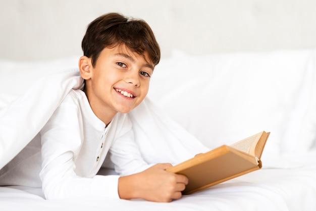 Menino sorridente coberto com cobertor durante a leitura Foto gratuita
