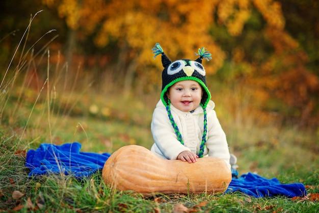 Menino sorridente com dois dentes em um boné de malha e roupas elegantes quentes, sentado na manta azul na grama com árvores de abóbora e outono Foto Premium