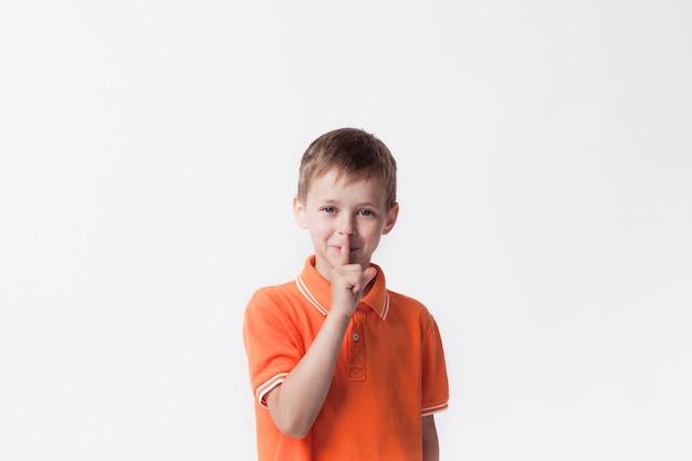 Menino sorridente com o dedo nos lábios, fazendo um gesto silencioso Foto gratuita