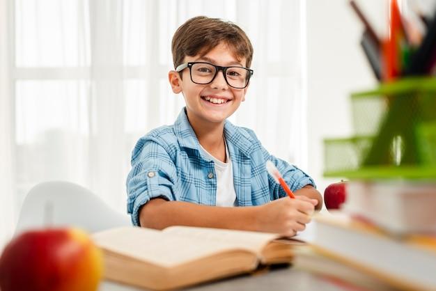 Menino sorridente de alto ângulo com óculos estudando Foto gratuita