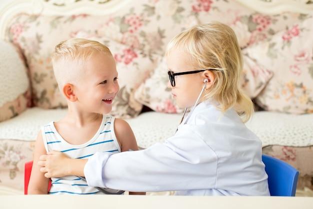 Menino sorridente e menina séria brincando com doutor Foto gratuita