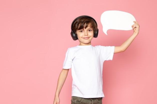 Menino sorridente em camiseta branca e calça jeans cáqui em fones de ouvido pretos, ouvindo música e discurso bolha Foto gratuita