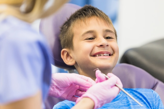 Menino sorridente, passando por tratamento odontológico na clínica Foto gratuita