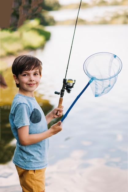 Menino sorridente, segurando, cana de pesca, e, rede, perto, a, lago Foto gratuita