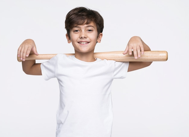 Menino sorridente segurando o taco de beisebol Foto gratuita
