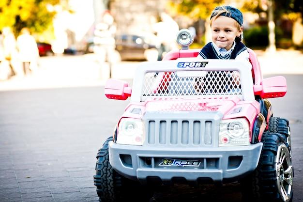 Menino tão pequeno e tão grande. criança, olhar, bravo, dirigindo, seu, brinquedo, outlander Foto gratuita
