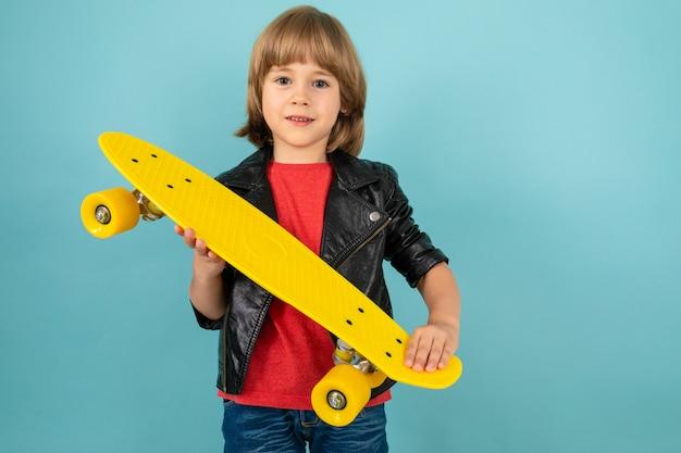 Menino tem skate amarelo nas mãos, sobre um fundo azul Foto Premium